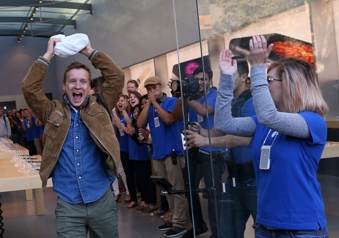 Patrick Tuntland holds up his new iPhone 6 as he leaves an Apple Store in Palo Alto, California.  (Photo by Justin Sullivan/Getty Images)